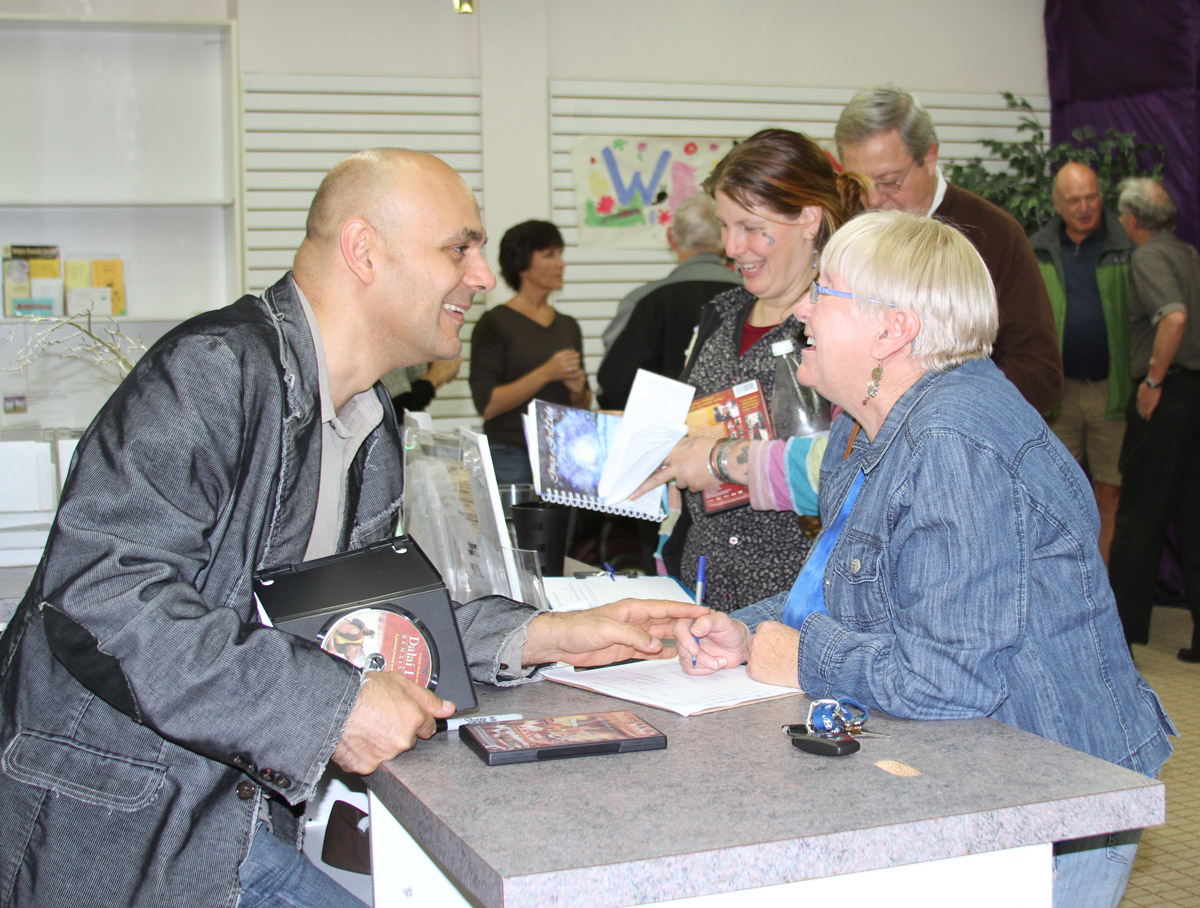 Director Khashyar Darvich signing DVDs and speaking with an audience member after a screening of 'Dalai Lama Awakening'