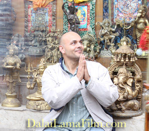 Photo of                                                           Director                                                           Khashyar                                                           Darvich                                                           sitting in                                                           front of a                                                           Buddhist                                                           statue store                                                           in Dharamsala,                                                           India